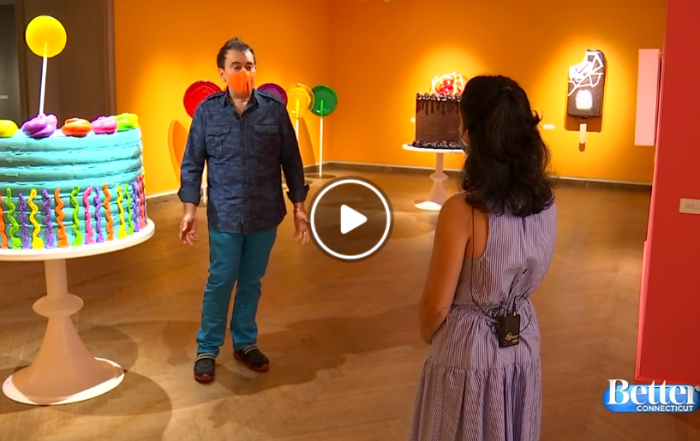 Sculptor Peter Anton stands in his museum exhibition amid large confectionery sculptures